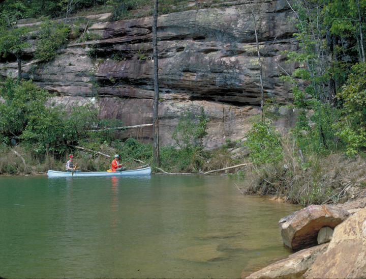 Two people canoe in a body of water in the Sipsey Wilderness. The water body is near the base of a large rock formation.